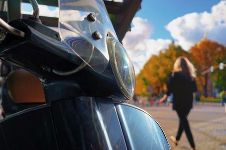 Скутер с фарой, припаркованной на фоне осеннего городского парка с проходящей девушкой с длинными волосами Фото со стока