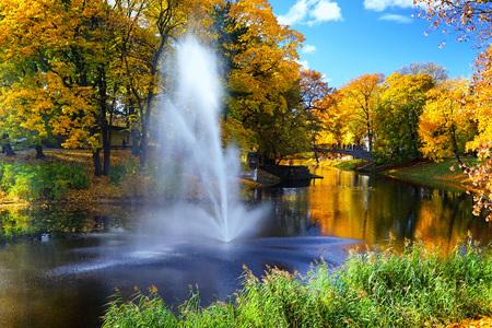 Городской парк города Риги с каналом с яркими осенними листьями на фоне голубого неба и отражениями в воде Фото со стока