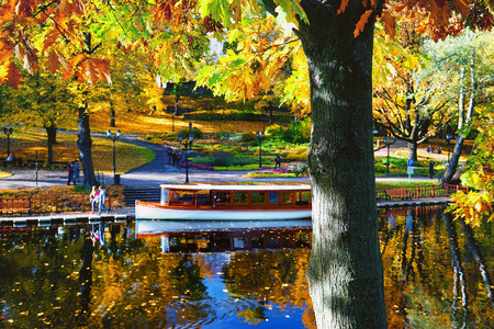 City park of the city of Riga with a canal with bright autumn leaves against the blue sky and reflections in the water