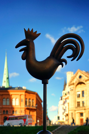 Weathervane in the form of a metal cockerel on the Dome Square in Riga on a sunny autumn day Фото со стока