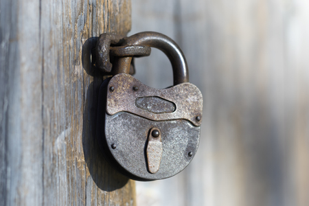Old iron lock with a lost key on a wooden door of an old house Stock Photo
