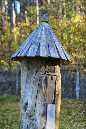 An ancient wooden beehive for bees with a base roof in an autumn forest