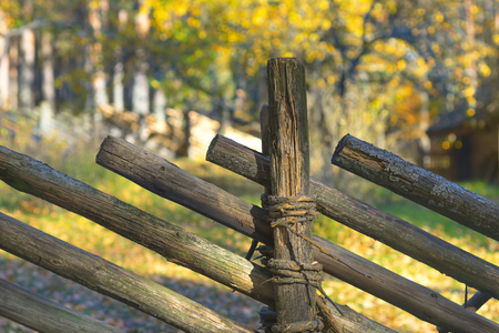 A fence of tilted wooden beams against the background of the autumn forest