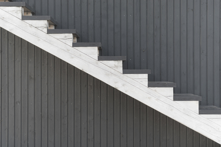 White staircase with steps up and down against the red wall background of vertical boards Фото со стока