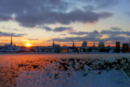 Horizon with spiers in the city of Riga in the winter on the background of frost on the glass at sunset