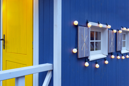 Windows with light bulbs on a blue painted wooden house wall with a yellow door