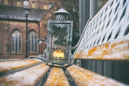 Vintage lantern with a burning wax candle on a bench on Dome Square in the ancient city of Riga Фото со стока