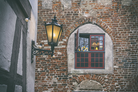Street yellow lamp on the wall of the house of classical German architecture in the courtyard of the old city of Riga