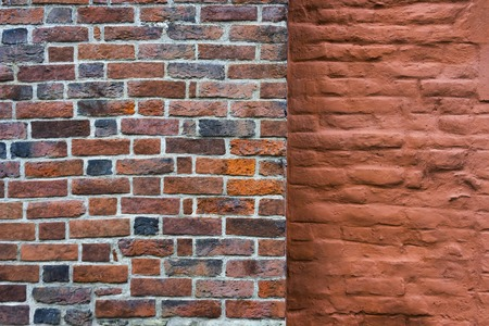 A wall of beautiful red bricks next to the painted wall of an ancient building in the city