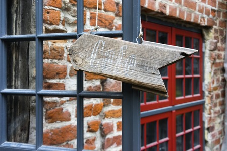 An inscription of a cafe on a wooden board with an arrow on the windows of a building in the old town of Riga Фото со стока