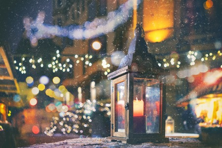 Vintage lamp with a burning candle in the background of the lights in a snowfall at the Christmas Market in the Old Town of Riga