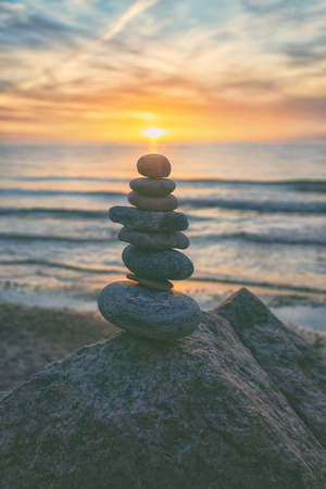 Pyramid of different stones against the background of sunset on the Baltic Sea in summer