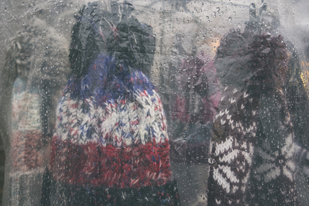 Winter knitted colorful hats under a transparent film with raindrops at the fair