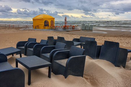 Wicker black tables and armchairs with a yellow summer cafe tent in a storm on the sandy beach of the Baltic Sea in summer