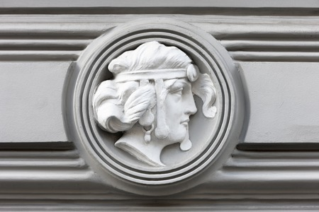 Bas-relief of a woman in a circle on an old house in the city of Riga Фото со стока
