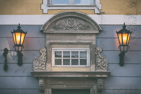 Two yellow lanterns on the facade of an old building with a sculpture in the old town of Riga