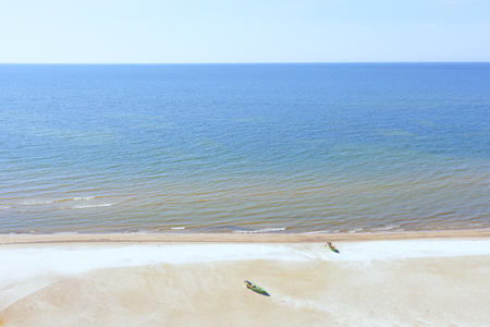 Yellow sand beach of the Baltic Sea with two wooden fishing boats and blue sea to the horizon Фото со стока