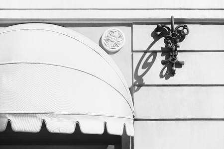 Marquise with ovals on a white wall above the entrance to Rigas house in a stylized graphic black and white image Фото со стока