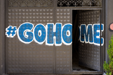Graffiti on the iron gate with Hashtag Go Home with the door open. Istambul