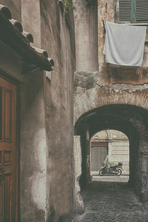 Classic Italian courtyard with linens on windows and a scooter in an arch in the center of Rome. Italy Фото со стока