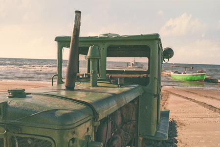 Green vintage tractor on the Baltic beach on the background of fishing boats at the pier Фото со стока
