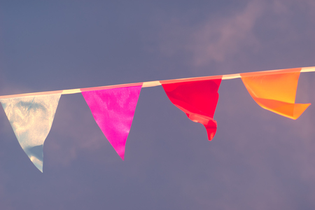 Triangular flags of different colors are sewn in a rope and sway in the wind against the sky. Blurry Stock Photo