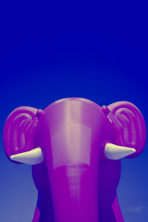 Pink big inflatable elephant with white tusks on a blue sky background