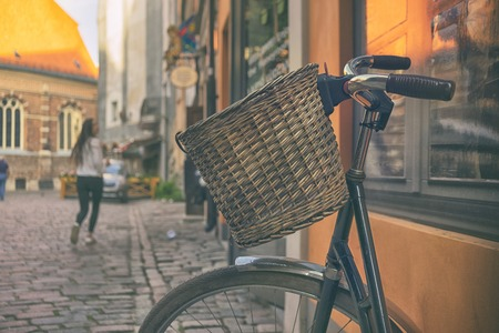 A bicycle with a basket on the steering wheel in the center of the old city of Riga against the backdrop of walking tourists on a summer day.
