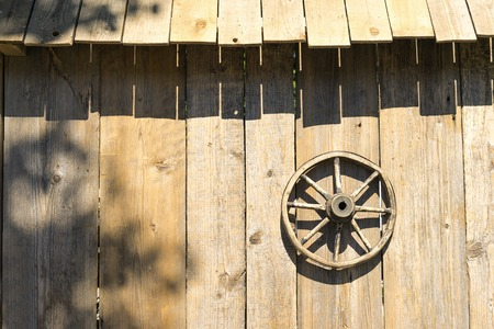 A wooden wheel hangs on the wall of a shed of boards with shadows from the roof