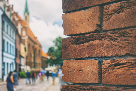 Red bricks on the facade of a building on the street with tourists in the old city of Riga on a summer day Фото со стока
