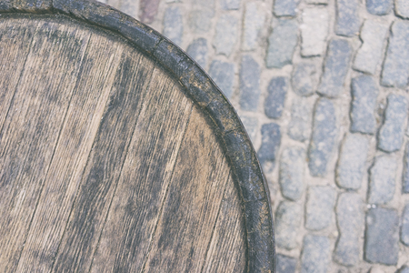 Wooden old barrel against the backdrop of the stones of the street