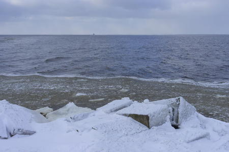 Ship on the horizon go to the sea in winter against a background of dark blue waves near the frozen shore in the snow Фото со стока