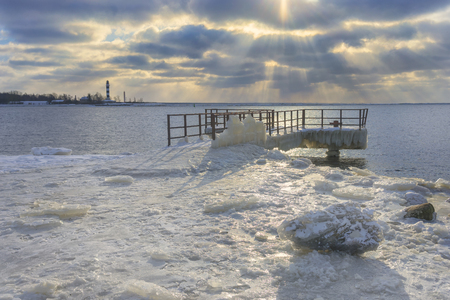 Berth in the ice against the lighthouse at the mouth of the river near the Baltic Sea with sun rays through the clouds in winter Фото со стока