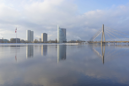 The Riga embankment near the Daugava river in a winter frosty day against the backdrop of a skyscraper and a cable-stayed bridge with reflection Фото со стока