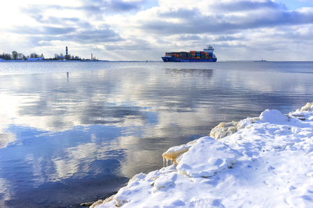 A cargo ship enters the mouth of the Daugava River past the lighthouse on a winter day in Latvia