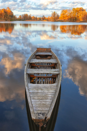 Wooden boat on lake water with reflection of white clouds and yellow trees in autumn