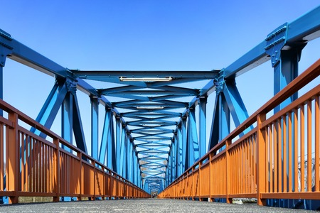 Iron structures of a pedestrian bridge with rails and arches on a sunny spring day