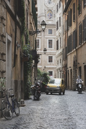 Different transport on the narrow street of Rome with lanterns and ancient buildings