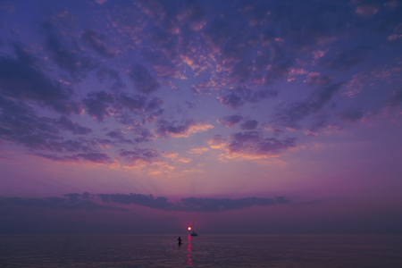 Purple sunset with a beautiful sky in the clouds with a sailboat and swimmer in calm water in the Baltic Sea