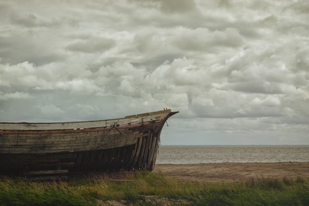Old broken wooden boat in the sand dunes of the Baltic Stock Photo