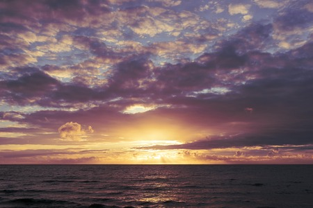 Purple sunset through orange clouds in the Baltic Sea on a summer evening