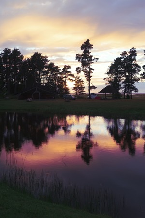 Sunset in camping with a purple reflection of clouds and pines in the lake water