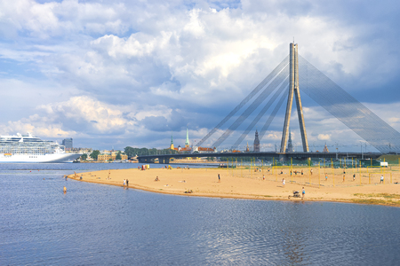 The capital of Latvia Riga in the spring with a view of the spires of cathedrals and churches on the background of the bridge on the Daugava river in Sunny day.
