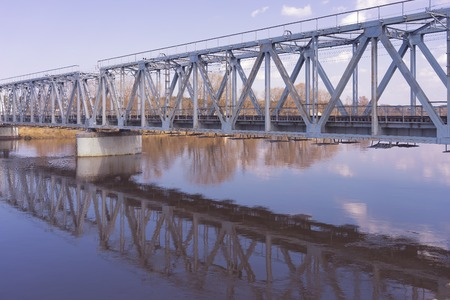 Railway bridge over the river in spring with reflection in water Stock Photo