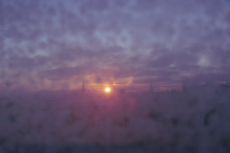 Sunset over Riga through a purple glass with snow on a winter evening. Blurry