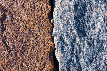 Two large stones with a beautiful texture touch the small stones in the slit