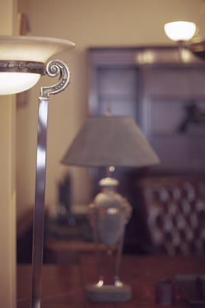 Fragment of a vintage lamp in the interior with a leather armchair and desk in the office Stock Photo