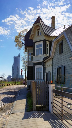 An old house in the street of Riga against the background of a modern skyscraper in the Kipsala area in the spring