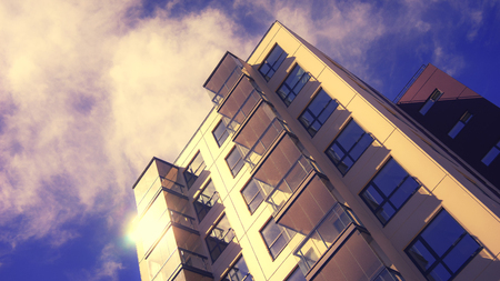 The facade of a new urban house with balconies against the background of a purple sky with clouds Stock Photo