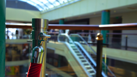 Red rope with chrome lock in an urban building with a glass roof and escalator
